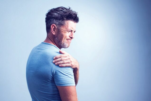 Mann fasst sich mit schmerzverzerrtem Gesicht an die Schulter