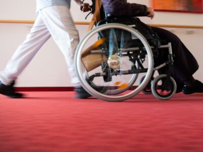 Pfleger und Frau im Rollstuhl