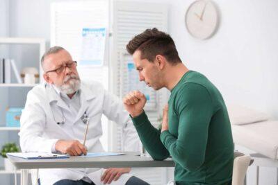 mann mit Erkältung beim Hausarzt