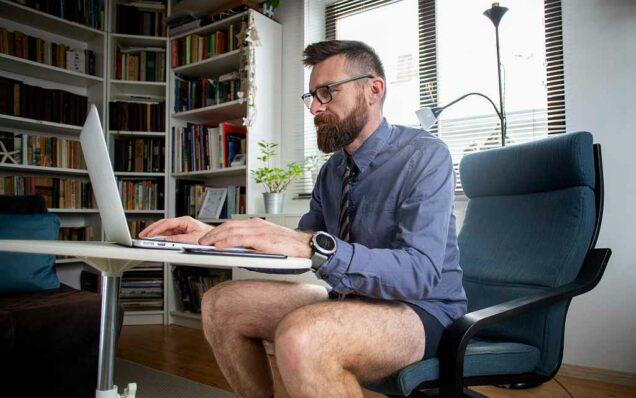 Mann sitzt in Unterhose am Schreibtisch im Homeoffice