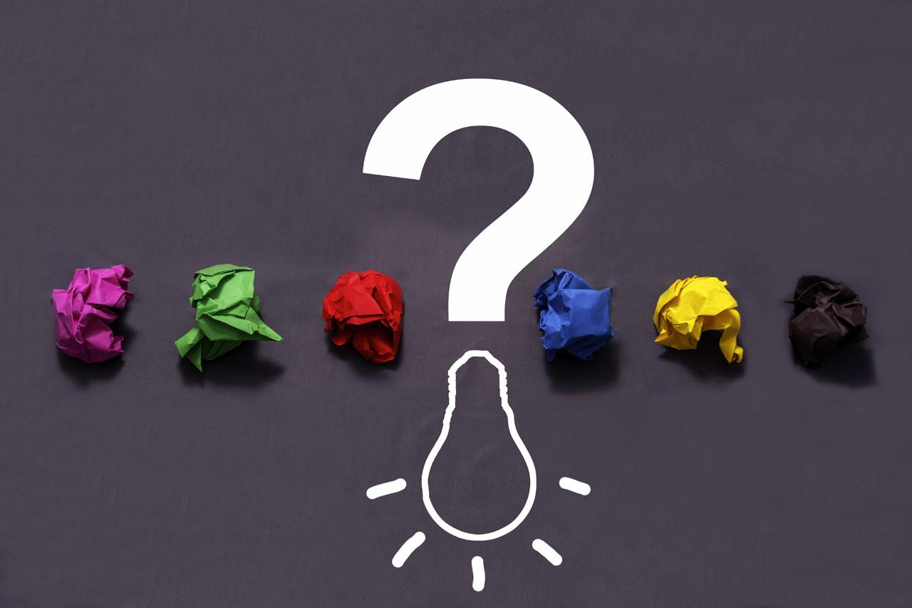 Ein Fragezeichen und Papierkugeln in den Farben der Parteien