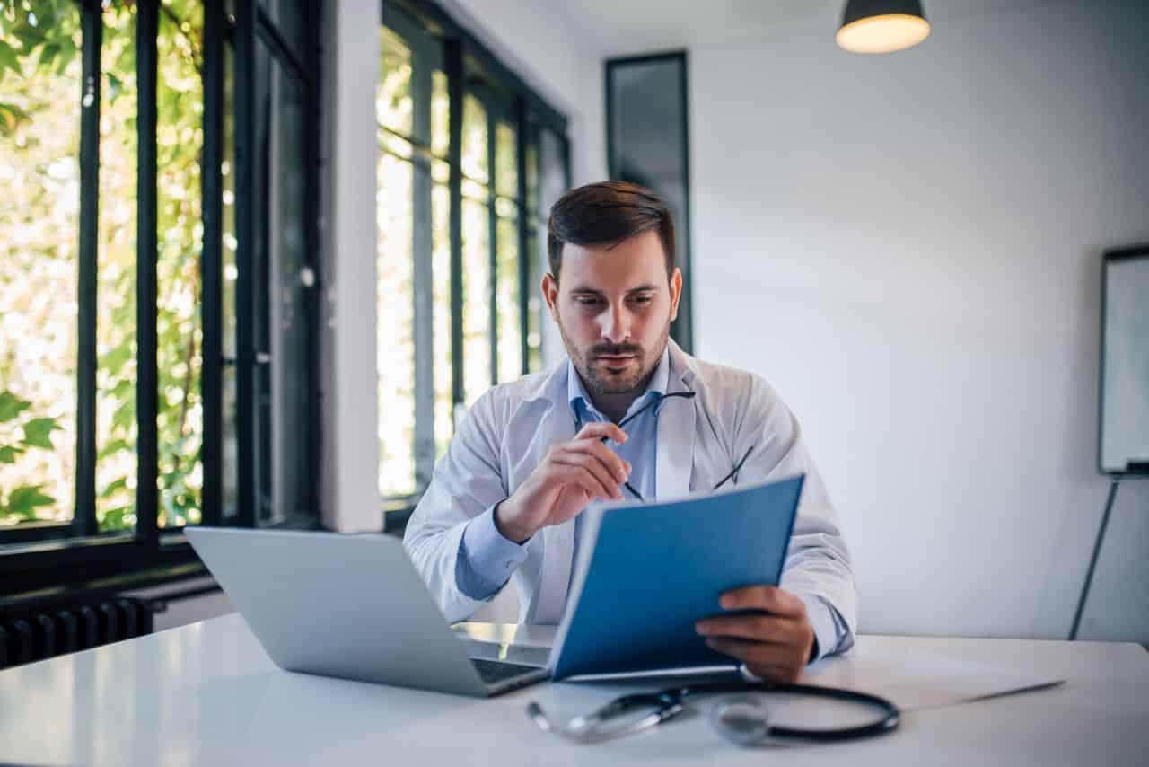 Arzt am Schreibtisch mit Unterlagen
