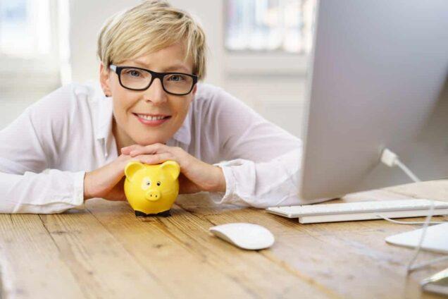 Frau mit Sparschwein vor Computer