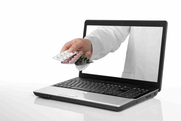 Hand mit Medikamenten ragt aus einem Notebook