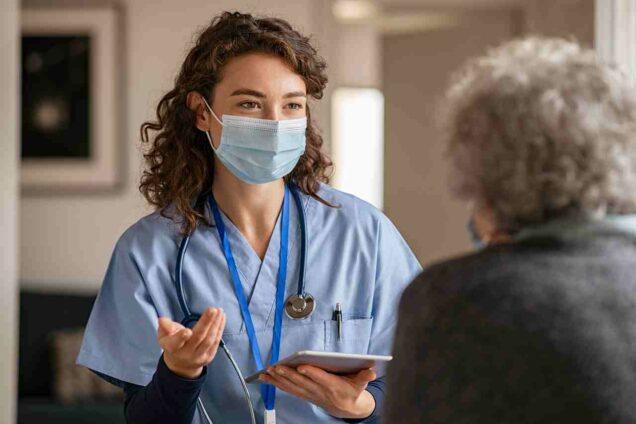 Krankenschwester mit Maske vor eienr Patientin