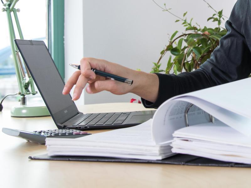 Frau mit Taschenrechner und Notebook