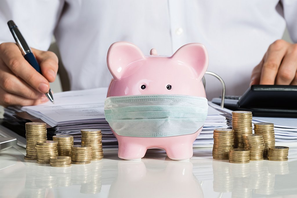 Sparschwein mit Mundschutz und Münzen