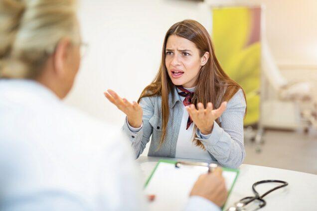 aufgeregte Patientin gestikuliert wild mit einem Arzt