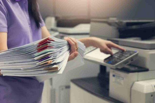 Bussinesswoman using copier machine to copy heap of paperwork in office.